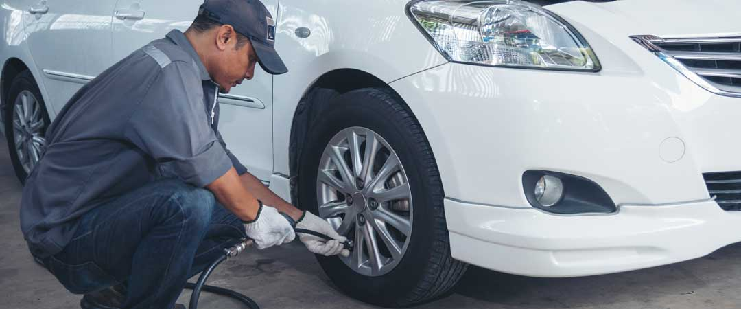 Mechanic adding air to car tire with an air compressor