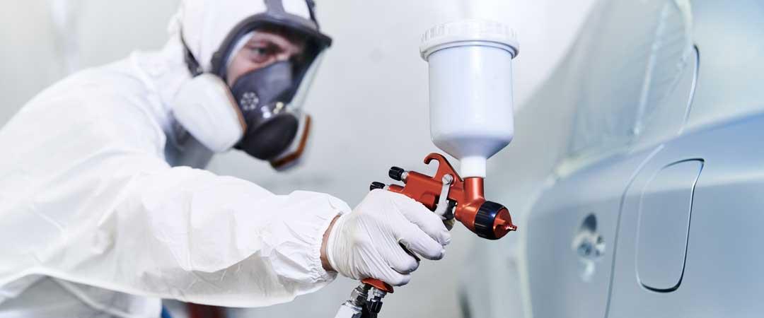 Man painting car with air compressor spray gun