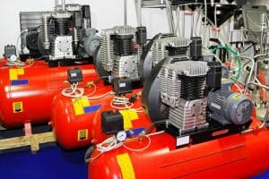 set of red air compressors arranged in line