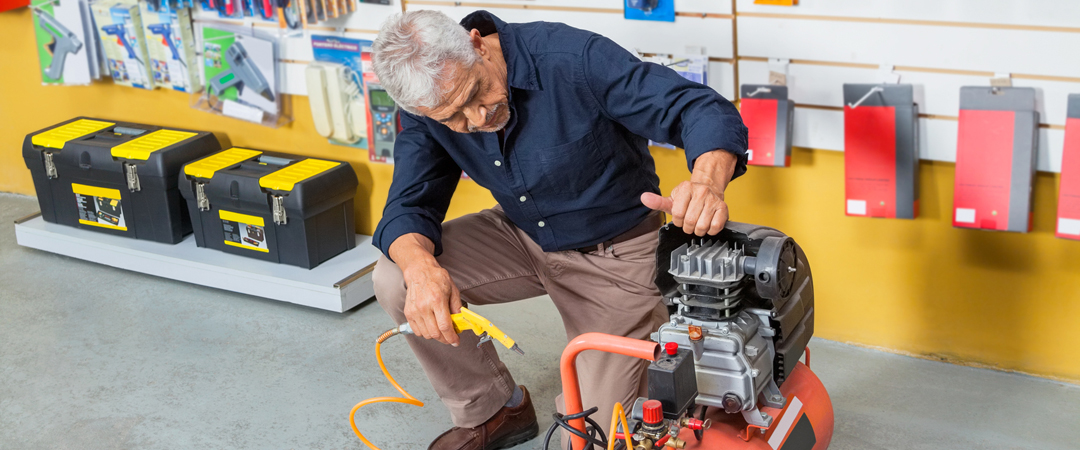 Man looking at an air compressor