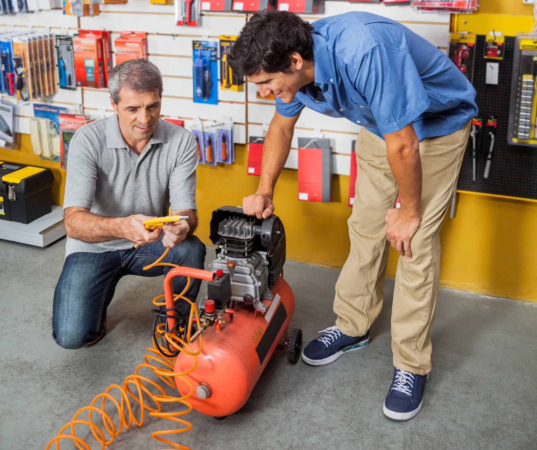 Two men looking an air compressor