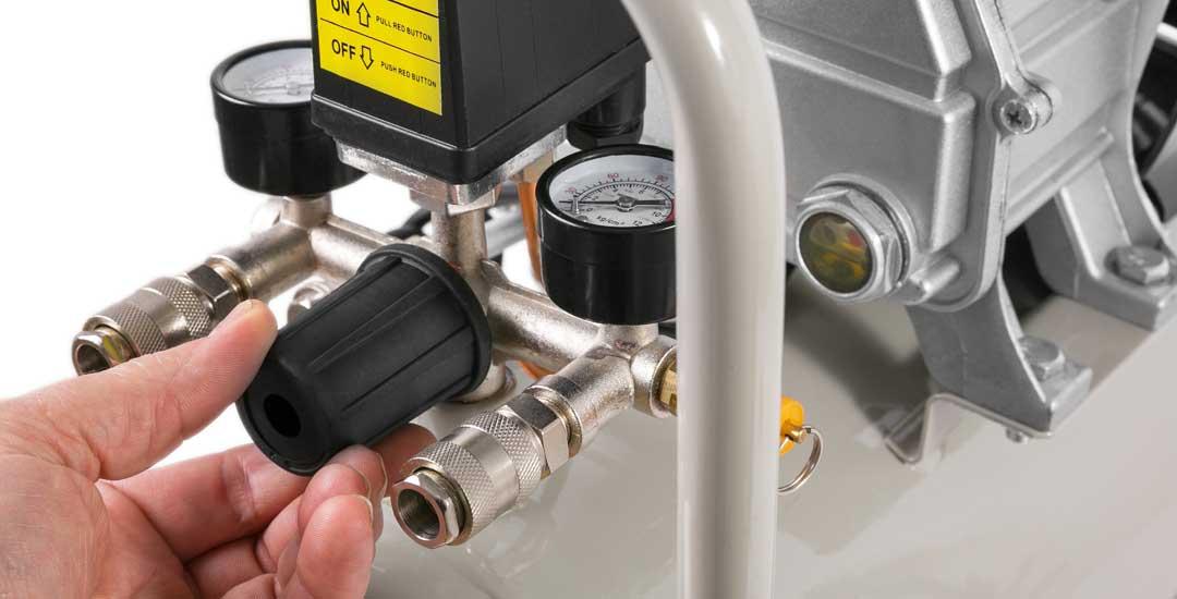 Man adjusting pressure on air compressor