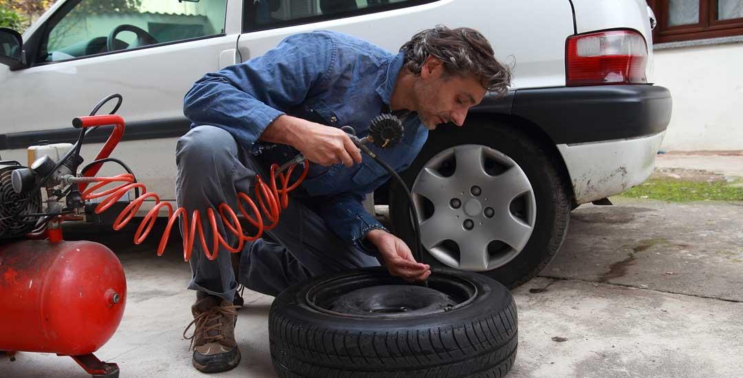 Man inflating a car tire