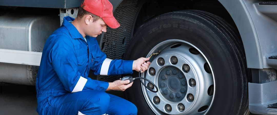 Mechanic Checking Tire Pressure on Semi Truck