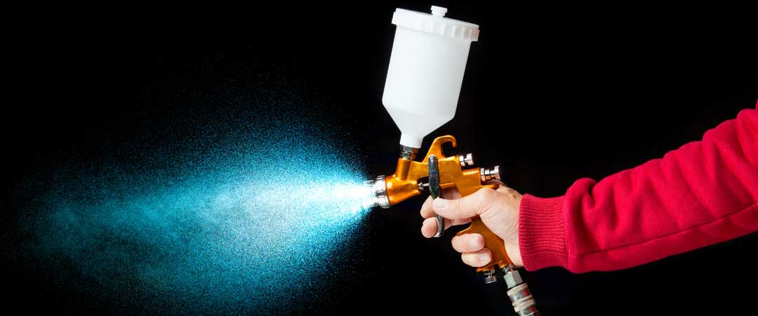 Man holding spray paint gun