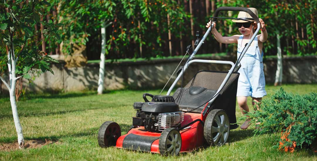 Little boy mowing yard