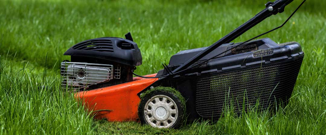 Red battery powered lawn mower cutting grass