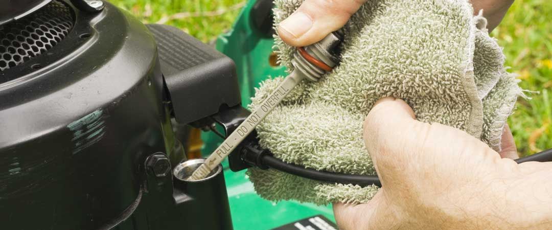 Checking oil on a gas lawn mower