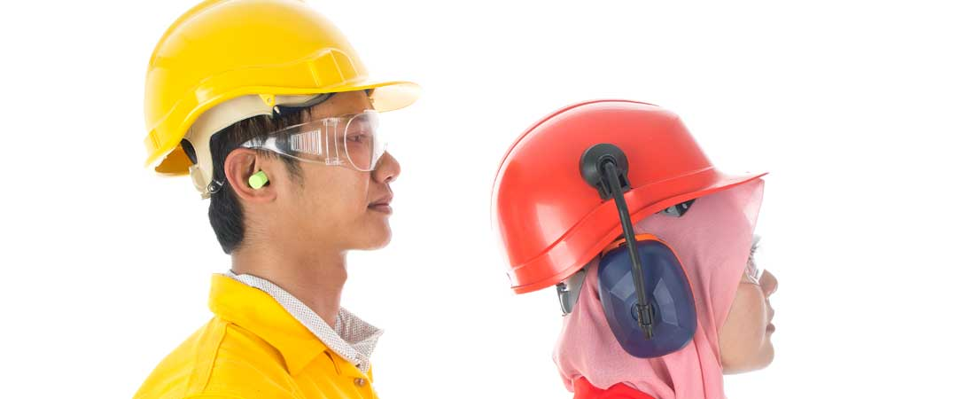 Man and woman wearing hard hats and ear protection