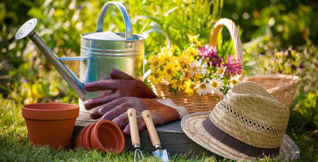 Water can, hat and tools in a flower garden